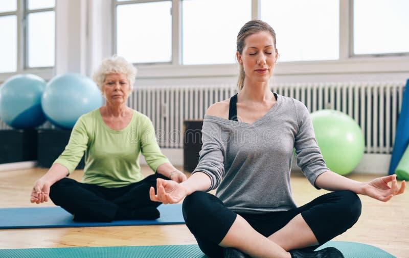 Frauen, die Yoga in der Klasse tun stockbild