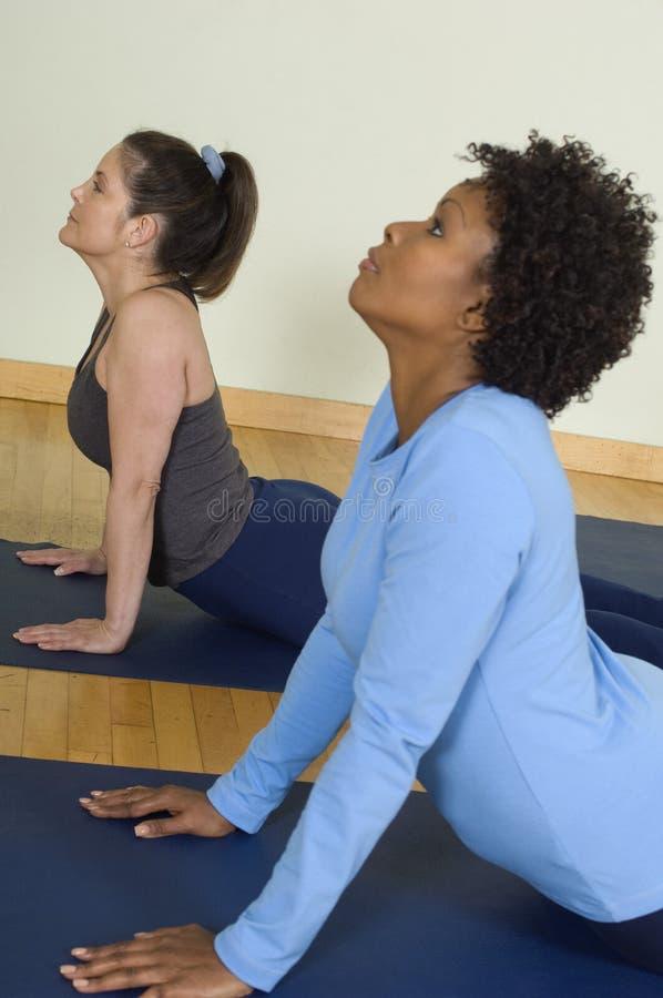 Frauen, die Yoga durchführen stockfotografie
