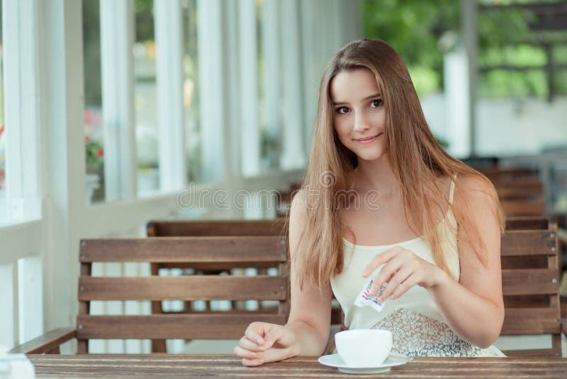 Frauen, die Zucker in einer Kaffee- oder Teetasse zugeben stockbild