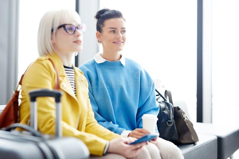 Frauen, die zusammen im Flughafen sitzen lizenzfreie stockbilder