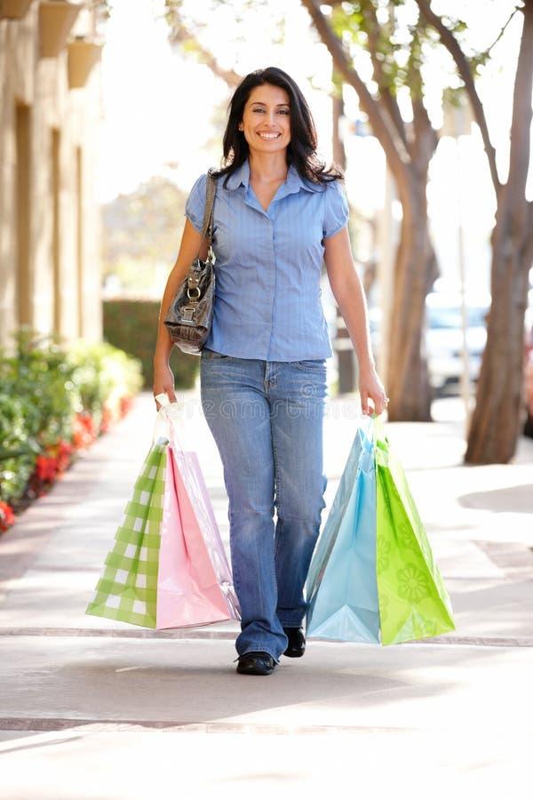 Frauen-Einkaufen, das hinunter die Straße geht lizenzfreies stockbild