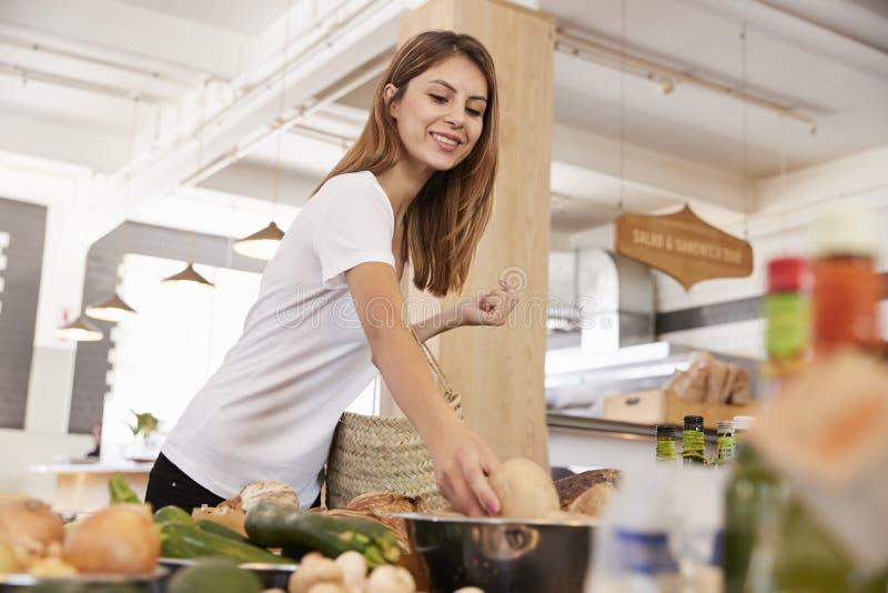 Frauen-Einkaufen für organisches Erzeugnis in den Delikatessen lizenzfreie stockfotos