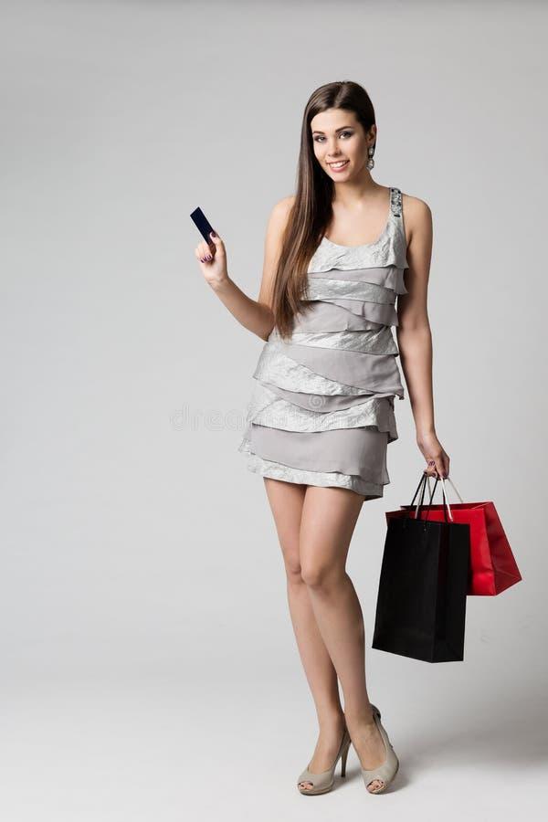 Frauen-Einkaufskleid mit Kreditkarte und Papiertüten, Mode-Modell-Full Length Studio-Porträt, Mädchen-Kaufen-Kleidung lizenzfreie stockbilder