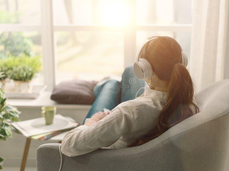 Frauen entspannen sich auf der Couch und hören Musik lizenzfreie stockfotografie