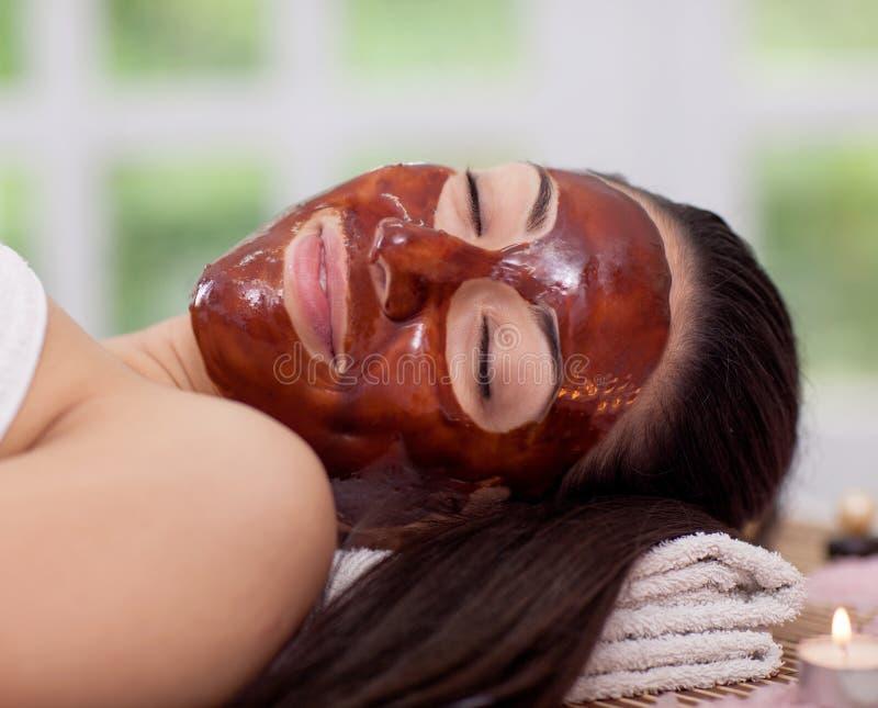 Frauen erhalten Schokoladentherapie auf seinem Gesicht im Badekurortsalon stockbild