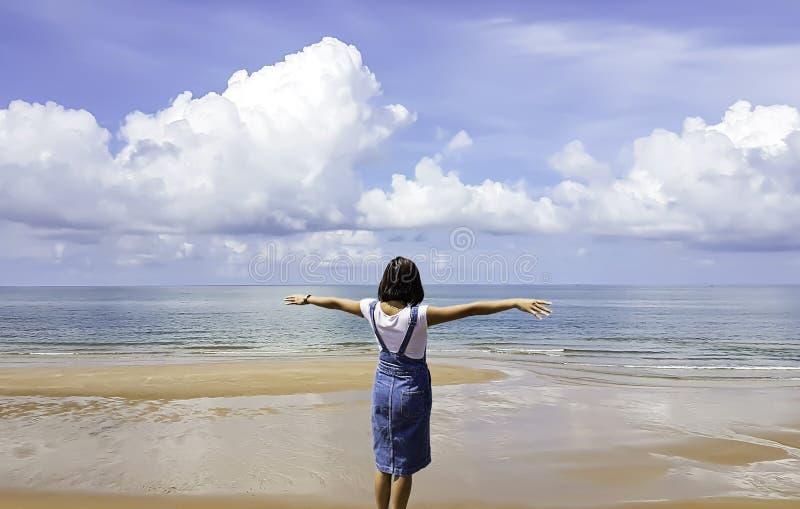 Frauen erheben ihre Arme am Strand und am Himmel in Chanthaburi in Thailand lizenzfreie stockfotos