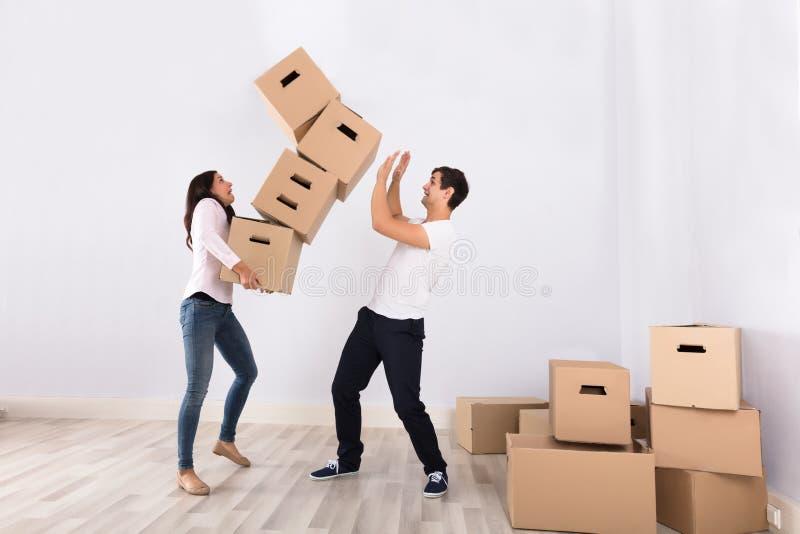 Frauen-fallende Pappschachteln über dem Mann stockfoto
