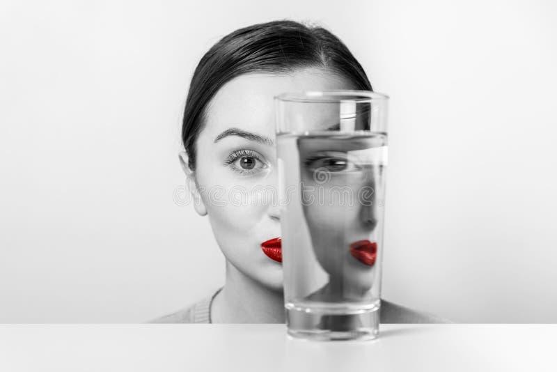 Frauen-Gesichts-Verzerrung im Wasser-Glas lizenzfreies stockfoto