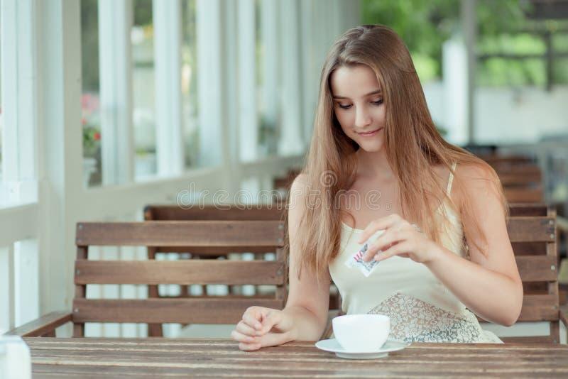 Frauen gießen Zucker auf Kaffeetasse stockfotografie