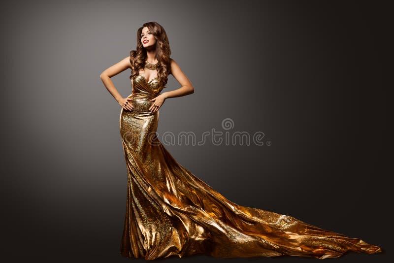 Frauen-Goldkleid, Mode-Modell Gown mit Zug des langen Schwanzes, Schönheits-Porträt stockbilder
