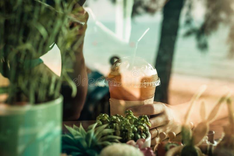 Frauen-Hände halten Eisteezitrone auf der hölzernen Tabelle und dem Kaktus nahe Fenstergras lizenzfreie stockfotografie