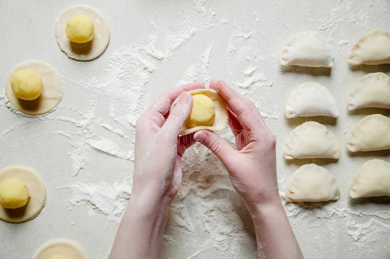 Frauen-Hände Sculpts Mehlklöße mit Kartoffeln auf weißem Hintergrund Traditionelle ukrainische Nahrung stockbild