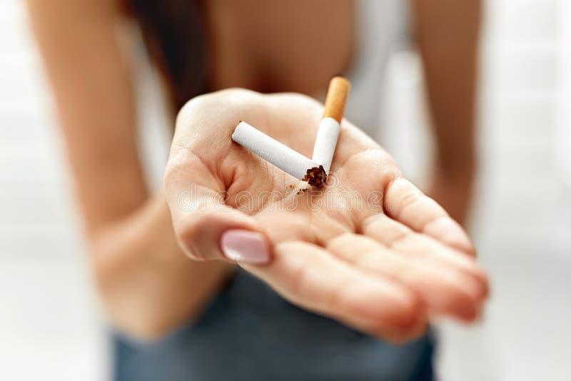 Frauen-Hand, die gebrochene Zigarette zeigt Ungesunder Lebensstil lizenzfreie stockbilder