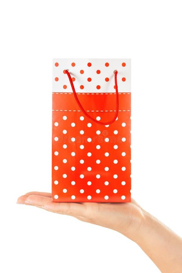 Frauen-Hand, die rote Geschenk-Tasche mit Geschenk hält stockfotos