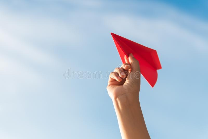 Frauen-Hand, die rote Papierrakete mit Hintergrund des blauen Himmels hält stockbilder