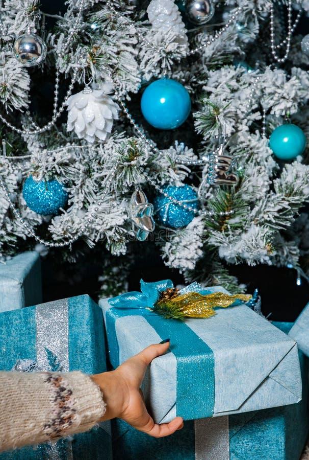 Frauen-Hand nimmt eine Weihnachtsgeschenkgeschenkbox stockbild