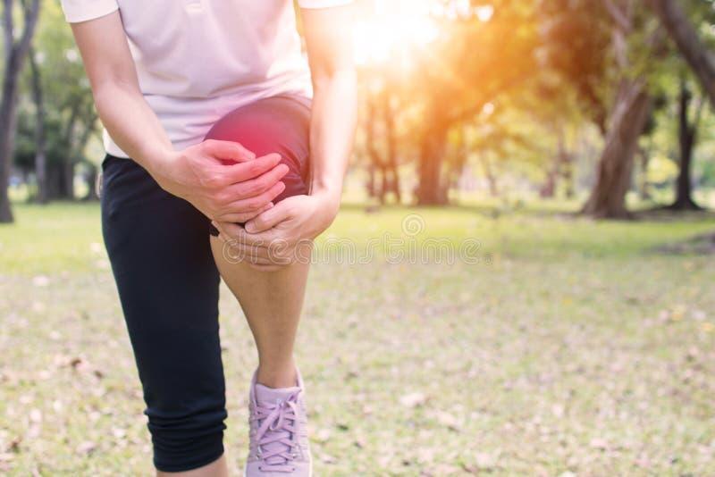 Frauen hat die Knieschmerz als Übung im Park lizenzfreie stockbilder