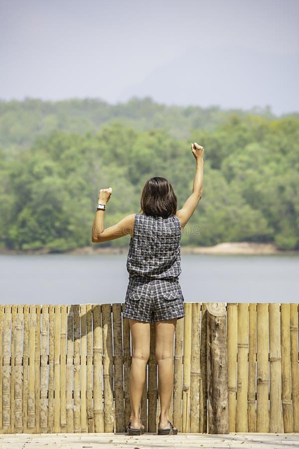 Frauen heben ihre Arme Hintergrundberge und -wasser an Chakrabongse-Reservoir, Prachinburi in Thailand an stockbild