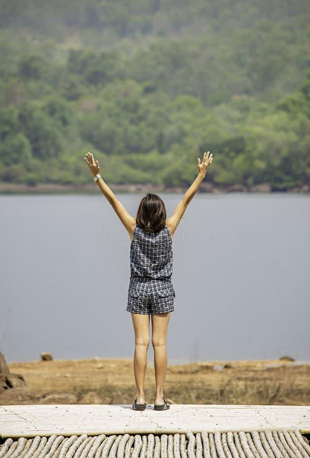 Frauen heben ihre Arme Hintergrundberge und -wasser an Chakrabongse-Reservoir, Prachinburi in Thailand an stockfoto
