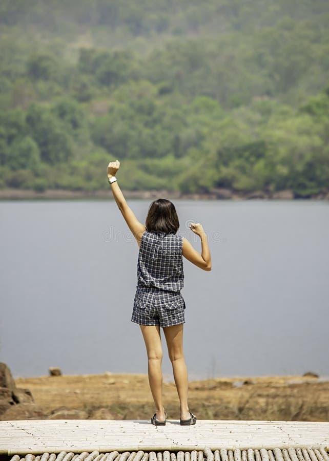 Frauen heben ihre Arme Hintergrundberge und -wasser an Chakrabongse-Reservoir, Prachinburi in Thailand an lizenzfreie stockfotografie