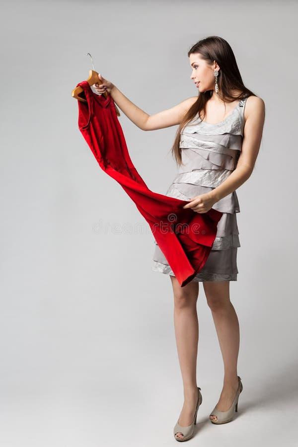 Frauen-Holding-rotes Kleid auf Aufhänger, schönes Mädchen, das Kleidung, Mode-Modell Studio Shot auf Weiß wählt lizenzfreies stockbild