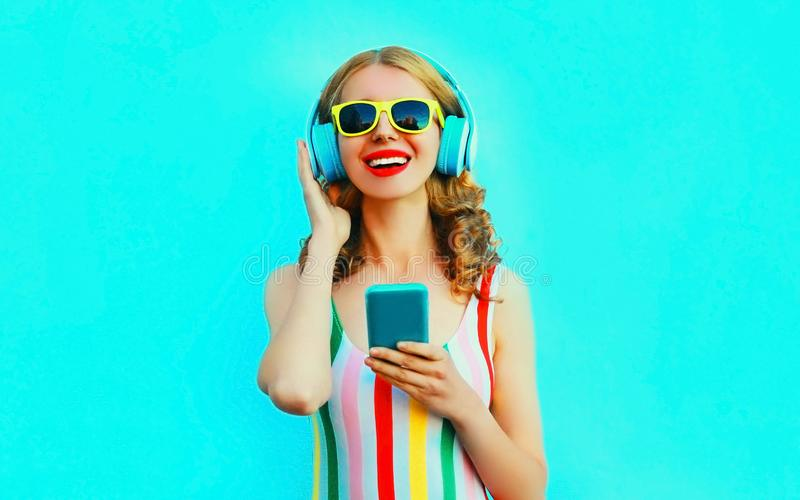 Frauen-Holdingtelefon des Portr?ts gl?ckliches l?chelndes, das Musik in den drahtlosen Kopfh?rern auf buntem Blau h?rt stockfotos