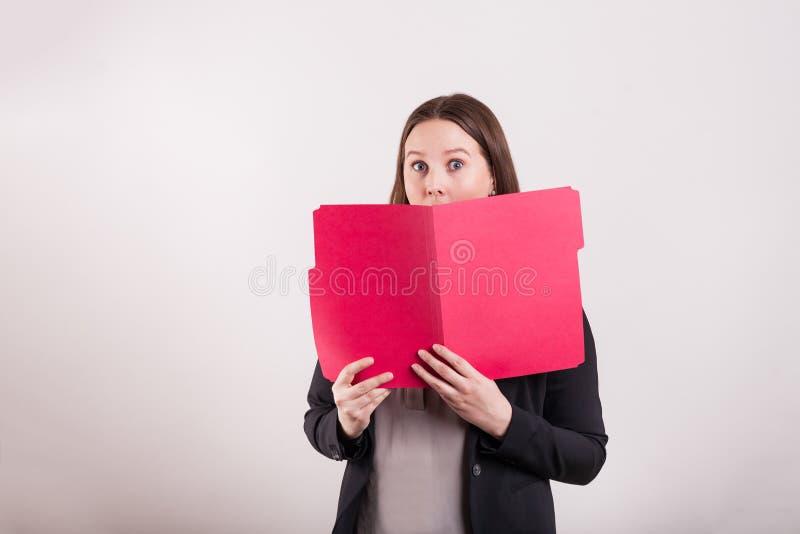Frauen im Anzug, der die rote Datei späht über Ordner hält lizenzfreies stockbild