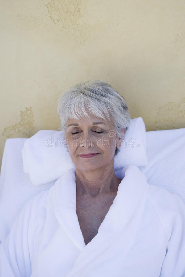 Frauen im Bademantel, der auf Klubsessel sich entspannt stockfotos
