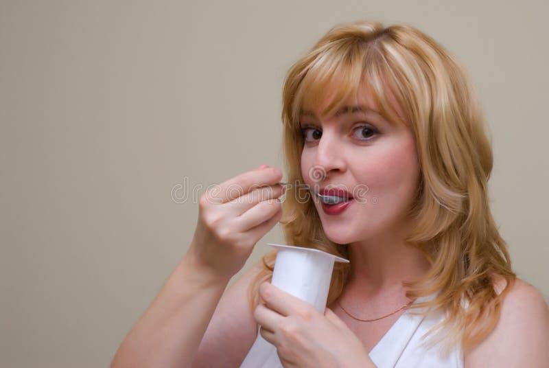Frauen isst Joghurt lizenzfreie stockfotografie