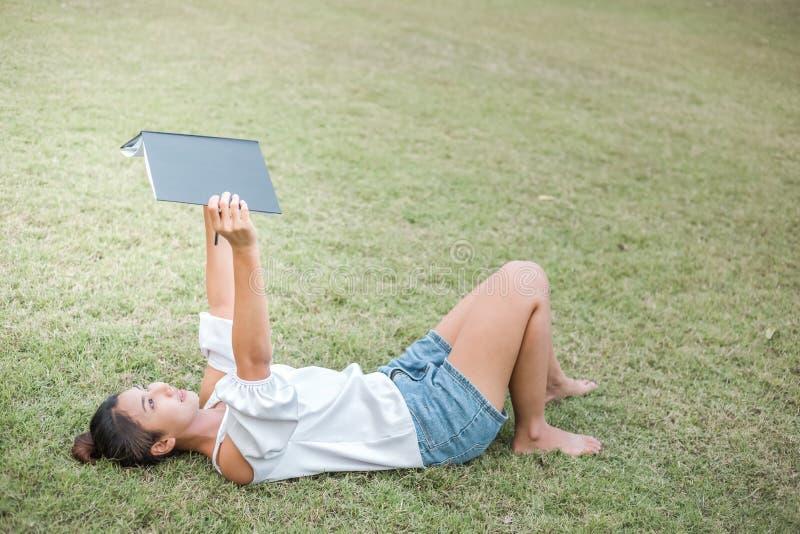 Frauen ist auf dem Gras und sch?n sie h?lt Buch sie tr?gt wei?es Kleid lizenzfreies stockbild