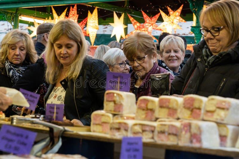 Frauen-Käufer, die auf einem Weihnachtsmarktstand grasen stockfotos