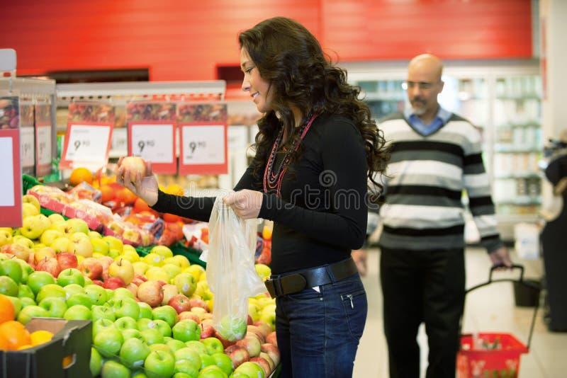 Frauen-kaufende Frucht stockbild