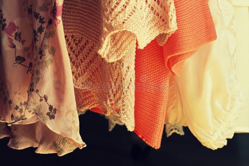 Frauen kleidet das Hängen an den Gestellen in einem Butikenspeicher stockbild