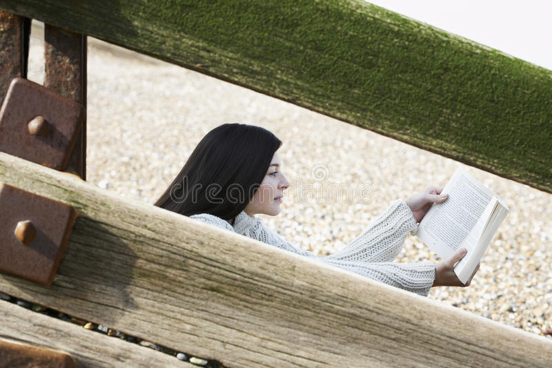 Frauen-Lesebuch beim Sitzen hinter Balustrade am Strand lizenzfreies stockbild