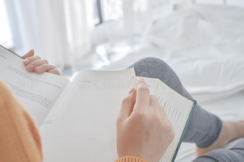 Frauen lesen ein Buch, das ein schwarzes Glas hält stockfotos