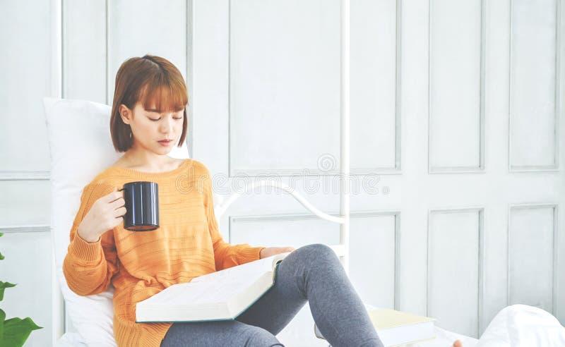 Frauen lesen ein Buch, das ein schwarzes Glas hält lizenzfreies stockfoto