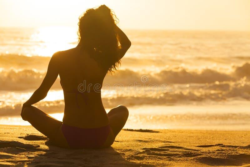 Frauen-Mädchen-sitzender Sonnenaufgang-Sonnenuntergang-Bikini-Strand lizenzfreie stockbilder