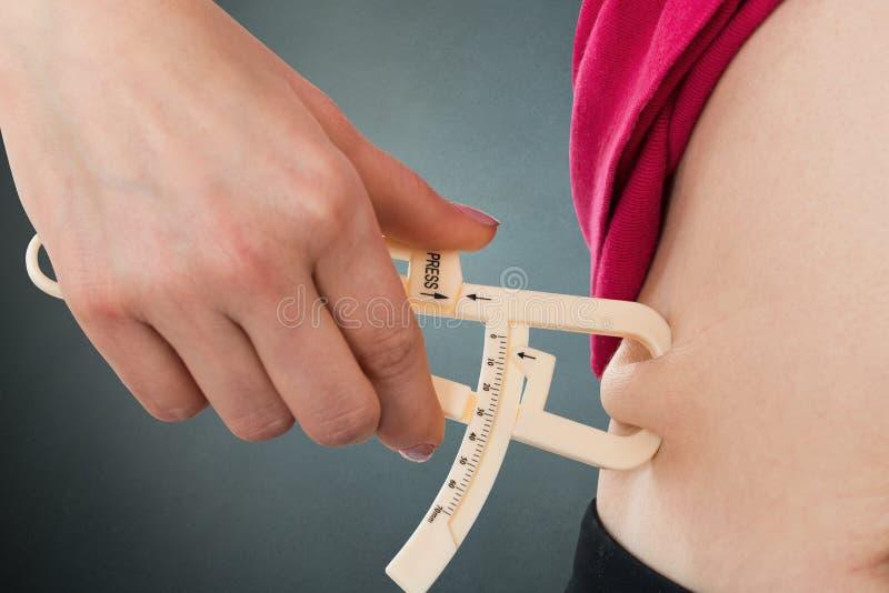 Frauen-messendes Magen-Fett mit Tasterzirkel stockfotografie