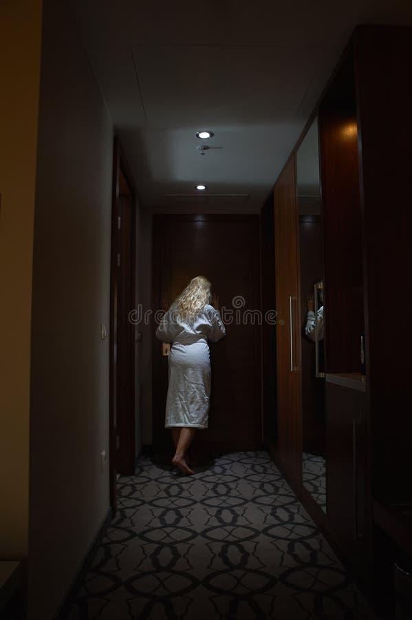 Frauen mit dem Bademantel, der durch das Guckloch schaut lizenzfreies stockbild