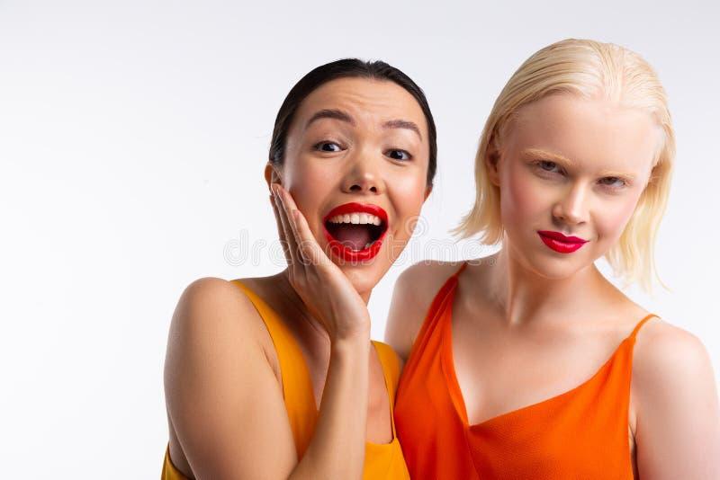 Frauen mit dem dunklen und blonden Haar, das helle rote Lippen hat stockbilder