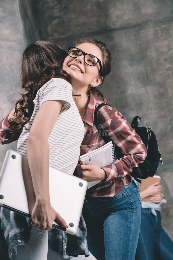 Frauen mit dem Schreibheft- und Laptopumarmen stockfoto