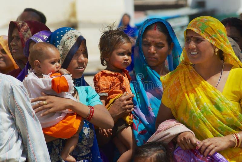 Frauen mit den Kindern, die Trachtenkleider tragen, passen religiöse Prozession an der Straße in Orchha, Indien auf stockfotografie