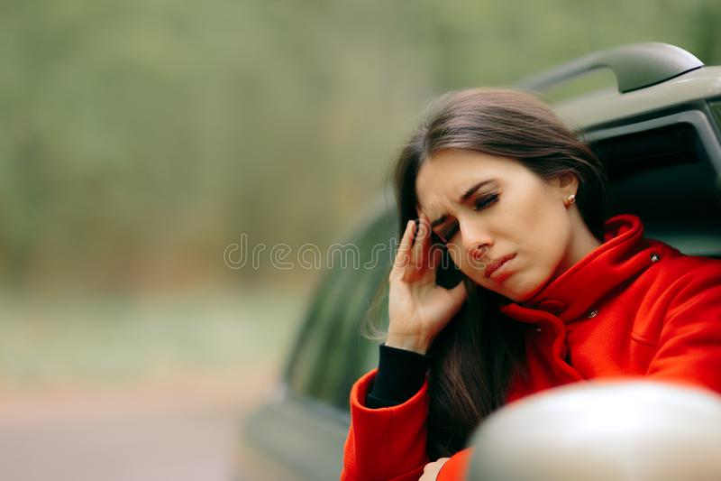 Frauen mit den schweren Kopfschmerzen, die unter Reisekrankheit leiden lizenzfreie stockfotografie