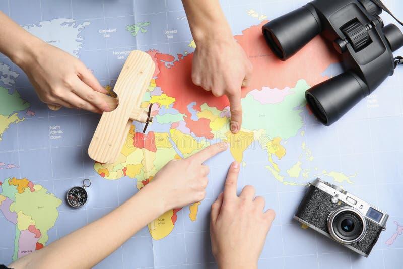 Frauen mit den touristischen Einzelteilen, die Ferien auf Weltkarte, Draufsicht planen lizenzfreie stockbilder