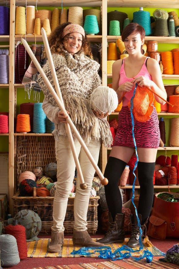 Frauen mit der kitting Stellung vor Garn verlegen stockbilder