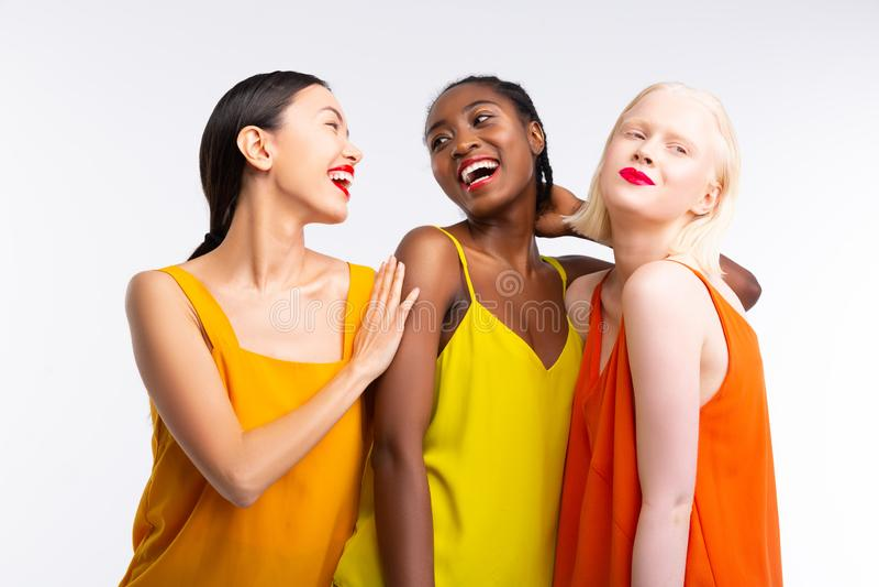 Frauen mit der unterschiedlichen Hautfarbe, die helle bunte Kleidung tr?gt lizenzfreie stockbilder