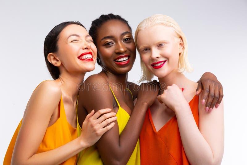 Frauen mit der unterschiedlichen Hautfarbe, die helle rote Lippen hat stockbild