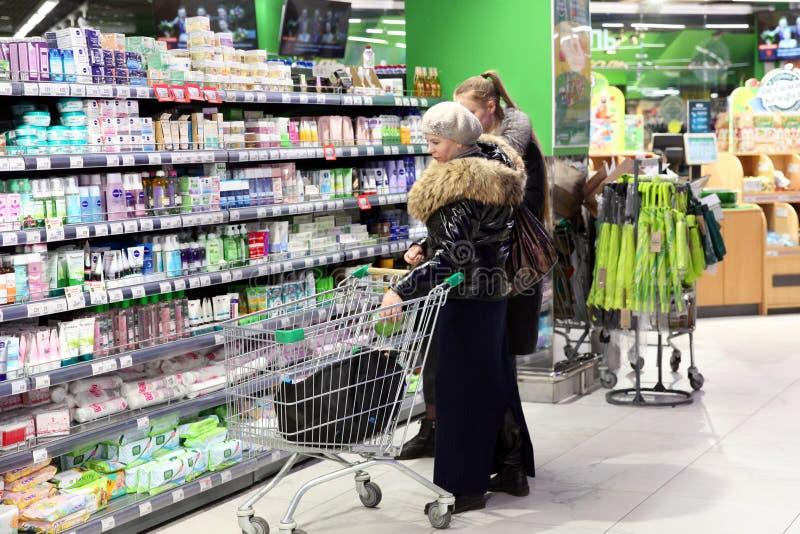 Frauen mit einem Wagen wählen Produkte in der kosmetischen Abteilung des Speichers moskau 05 02 2019 lizenzfreies stockbild