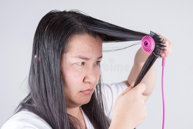 Frauen mit Haarrollen sind über Haarprobleme ernst stockbilder
