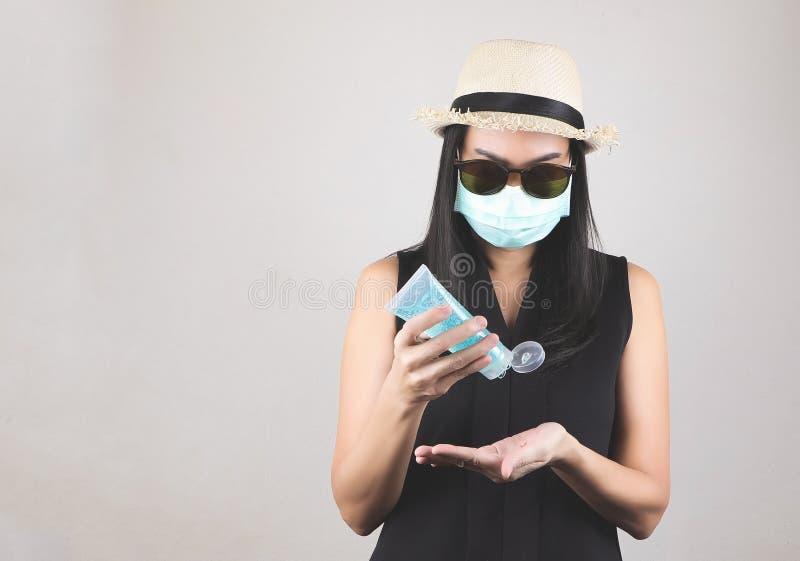 Frauen mit Hut und Sonnenbrille zum Schutz vor Sonnenlicht und mit hygienischer Maske, die Hand mit Alkoholgel zum Schutz vor Son lizenzfreie stockbilder